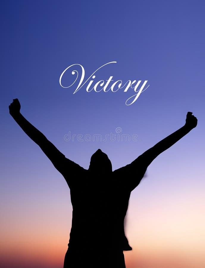 Homme célébrant au coucher du soleil avec le texte de victoire photo libre de droits