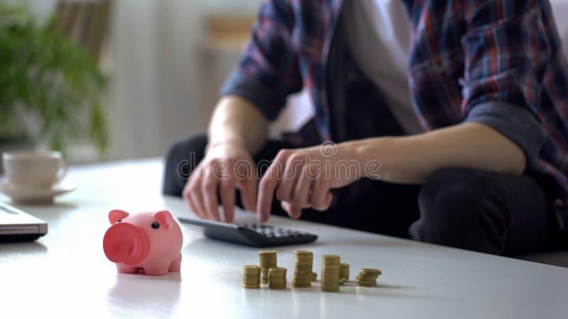Homme calculant l'argent, pièces de monnaie économisantes à la tirelire, planification de budget de famille images libres de droits