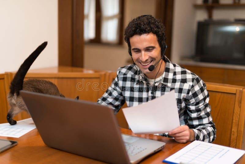 Homme caressant son chat tout en travaillant à la maison image libre de droits