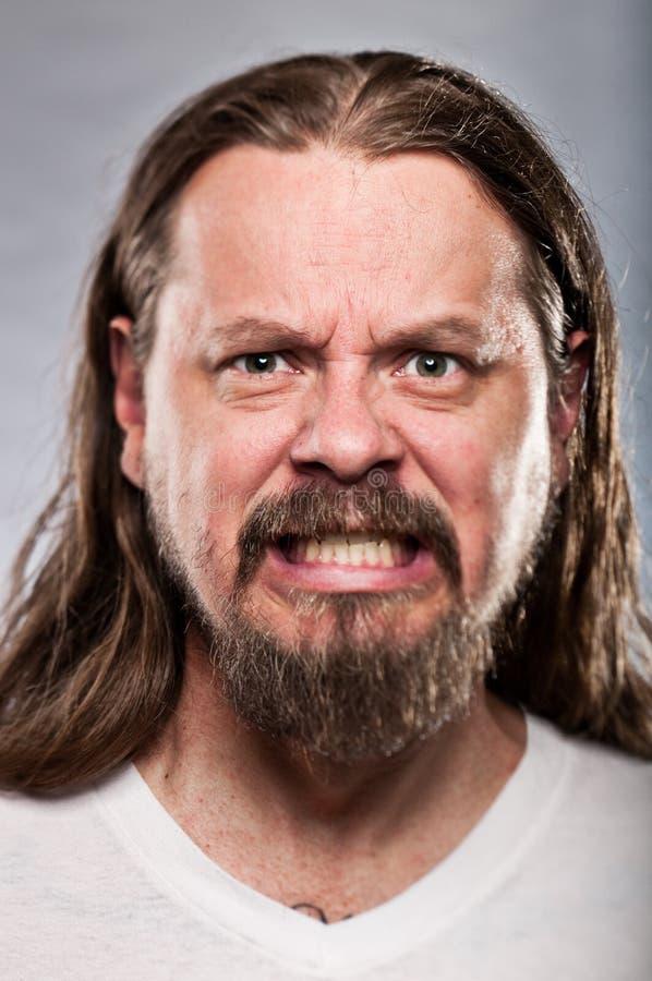 Homme caucasien avec de longs cheveux semblant fâchés photos libres de droits