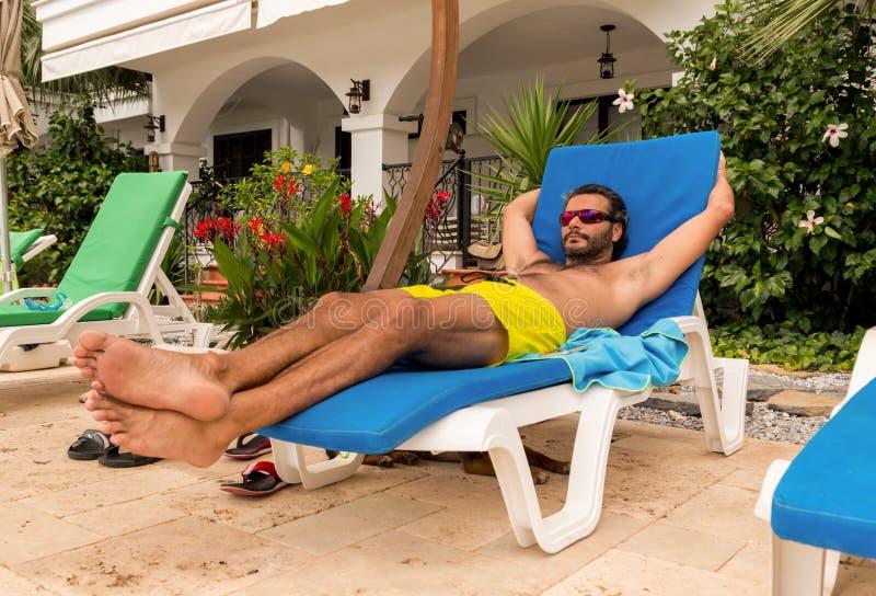 Homme caucasien barbu avec des lunettes de soleil se reposant sur un lit pliant dans une station de vacances photos libres de droits