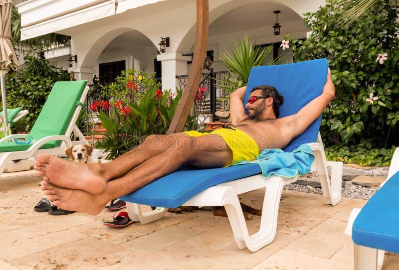 Homme caucasien barbu avec des lunettes de soleil se reposant sur un lit pliant dans une station de vacances images libres de droits