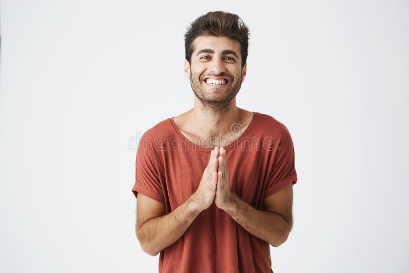 Homme caucasien bel dans le T-shirt rouge souriant heureusement et des mains de applaudissement étonné avec le cadeau d'anniversa photographie stock libre de droits