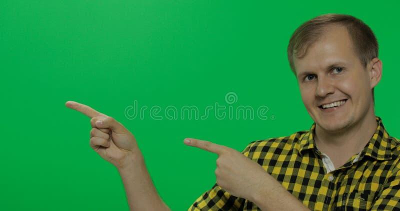 Homme caucasien dans la chemise jaune montrant quelque chose Endroit pour votre logo ou texte images stock