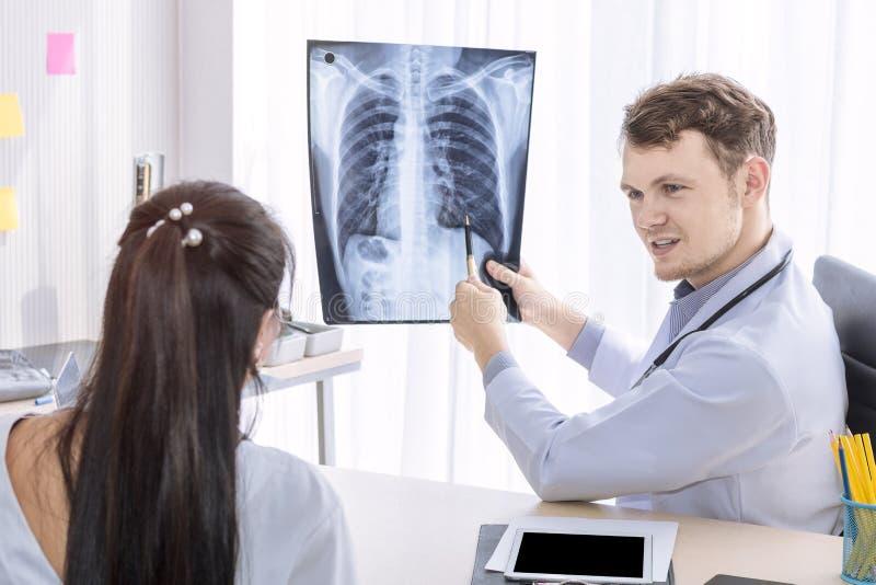 Homme caucasien de professionnels médicaux tenant le rayon X et la conversation photo stock