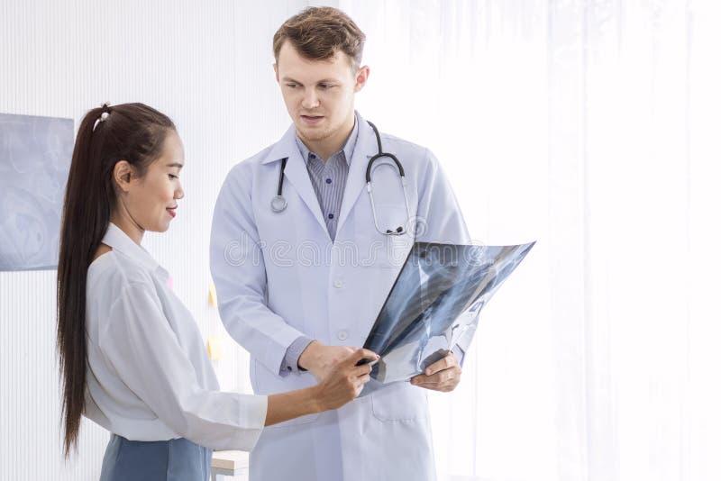 Homme caucasien de professionnels médicaux tenant le rayon X et la conversation photos stock