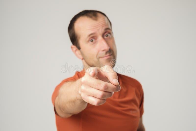 Homme caucasien de sourire dans le T-shirt orange dirigeant le doigt à vous photos stock