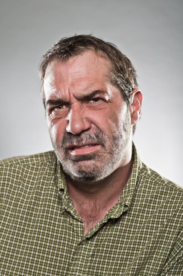 Homme caucasien mûr semblant le portrait grincheux photographie stock