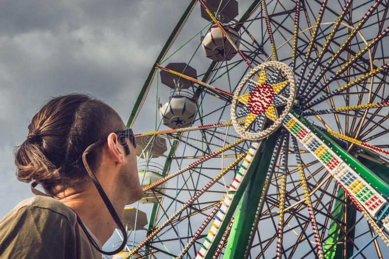 Homme caucasien observant la roue de ferris photo stock