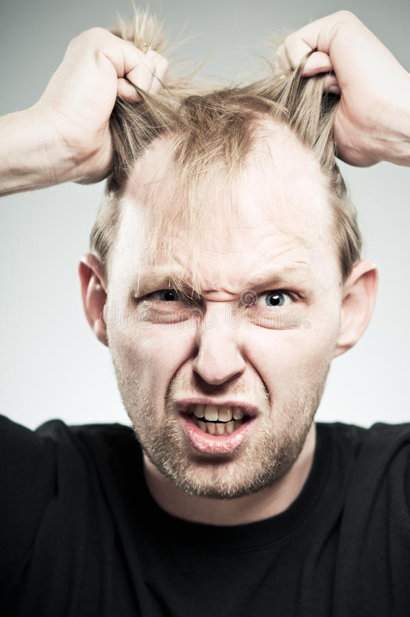 Homme caucasien retirant des cheveux avec la frustration photographie stock libre de droits
