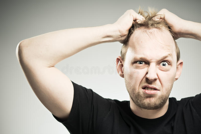Homme caucasien retirant des cheveux avec la frustration photo stock