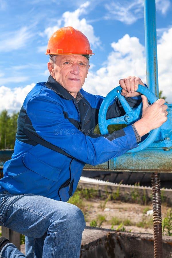 Homme caucasien supérieur dans un uniforme fonctionnant avec la valve de tuyau images libres de droits