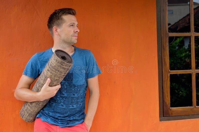 Homme caucasien tenant le tapis de yoga dans les mains et la position près du fond rouge photographie stock