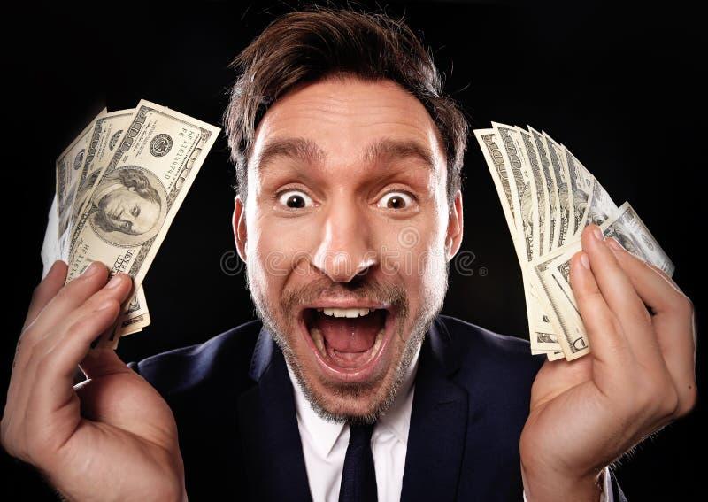 Homme chanceux tenant l'argent de billet d'un dollar 100 dans sa main image libre de droits