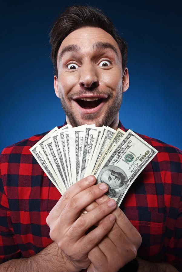 Homme chanceux tenant l'argent de billet d'un dollar 100 dans sa main photographie stock libre de droits