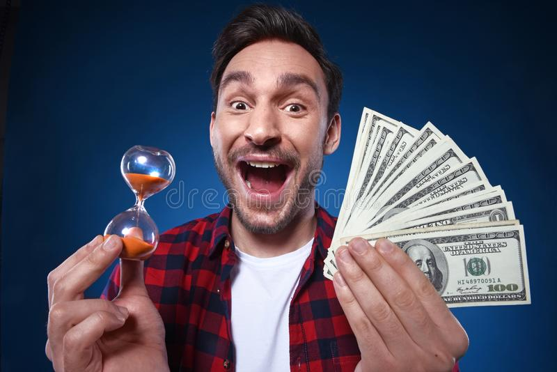Homme chanceux tenant l'argent et le sablier de billet d'un dollar 100 dans sa main photographie stock libre de droits