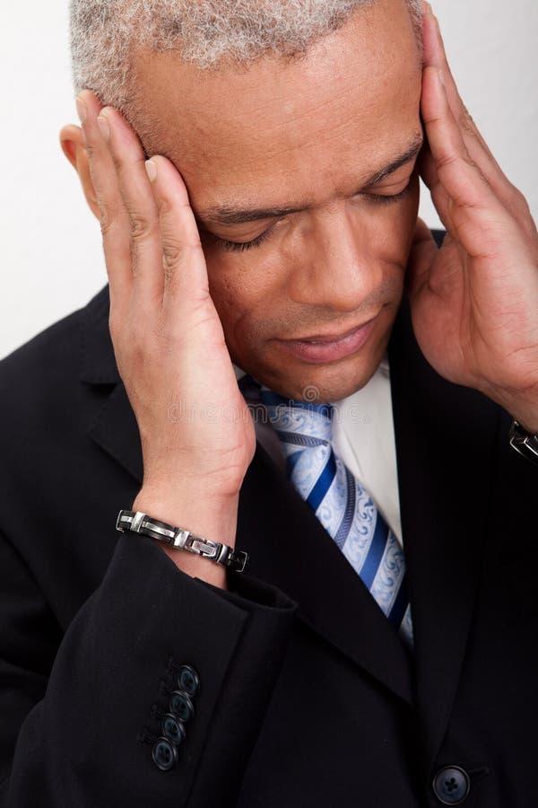 Homme chargé d'homme d'affaires avec le mal de tête photographie stock
