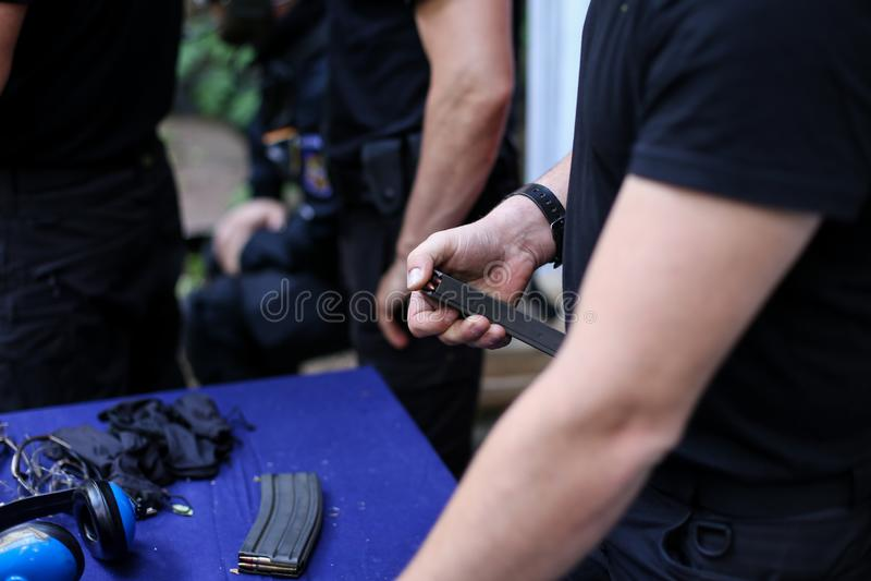 Homme chargeant des cartouches de 9mm dans une agrafe d'arme à feu image libre de droits