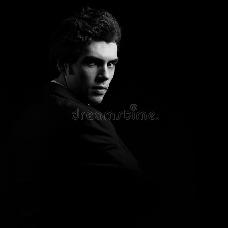 Homme charismatique bel semblant sérieux dans l'ombre foncée dramatique photos stock