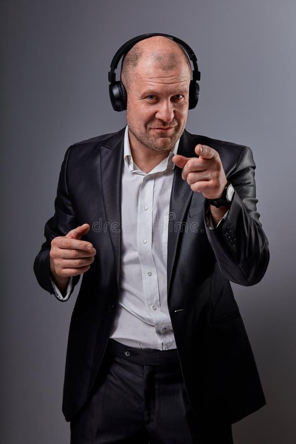 Homme chauve émotif heureux écoutant la musique dans l'écouteur sans fil et montrant le doigt sur vous sur le fond gris-foncé clo images libres de droits