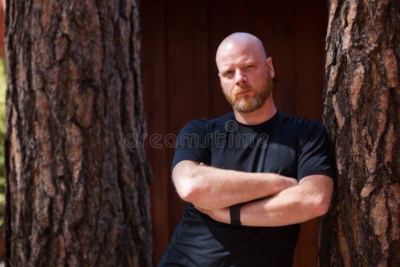 Homme chauve avec une barbe et des bras croisés images libres de droits