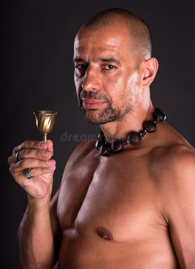 Homme chauve bel nu tenant le petit verre photo stock