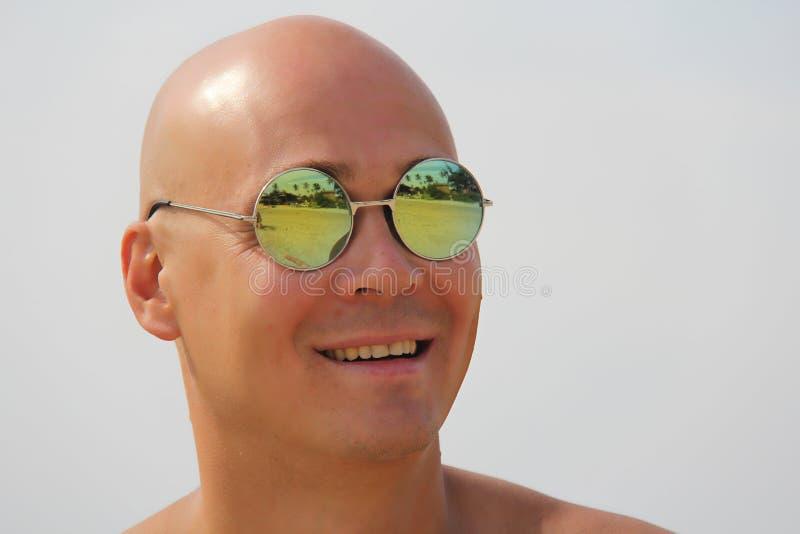 Homme chauve dans des lunettes de soleil de miroir Un bel homme bronzé sur le vacatio image stock