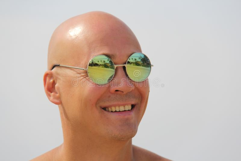 Homme chauve dans des lunettes de soleil de miroir Un bel homme bronzé sur le vacatio photographie stock