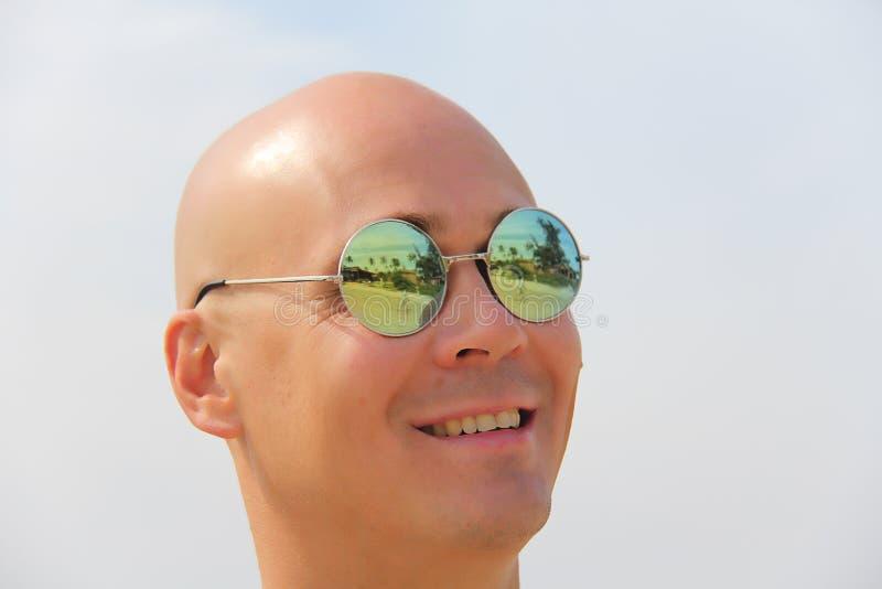 Homme chauve dans des lunettes de soleil de miroir Un bel homme bronzé des vacances, souriant Portrait d'un plan rapproché d'homm photos stock