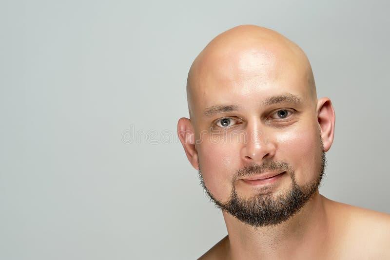 Homme chauve de sourire attirant sur le fond gris dans le studio photos libres de droits