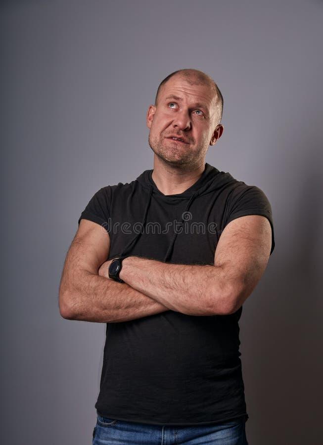 Homme chauve de sourire de pensée d'amusement avec les bras pliés dans la chemise occasionnelle noire recherchant sur le fond gri images stock