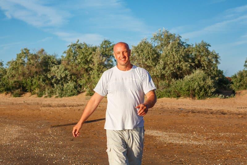 Homme chauve heureux marchant sur la plage dans des vêtements blancs images libres de droits