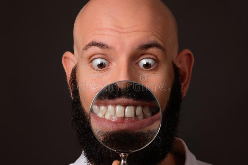 Homme chauve montrant ses dents par l'intermédiaire de la loupe sur le fond foncé photographie stock