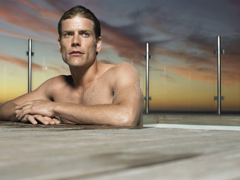 Homme chez The Edge de piscine extérieure au crépuscule photographie stock libre de droits