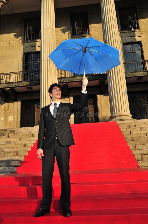 Homme chinois asiatique retenant le parapluie pour la protection photos stock