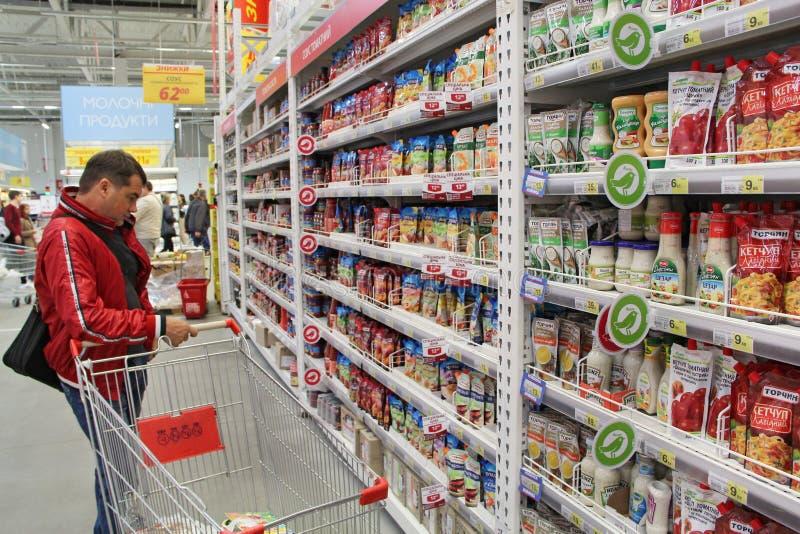 Homme choisissant dans des marchandises de supermarché Assortiment des sauces et de mayonnaise à ketchup images libres de droits