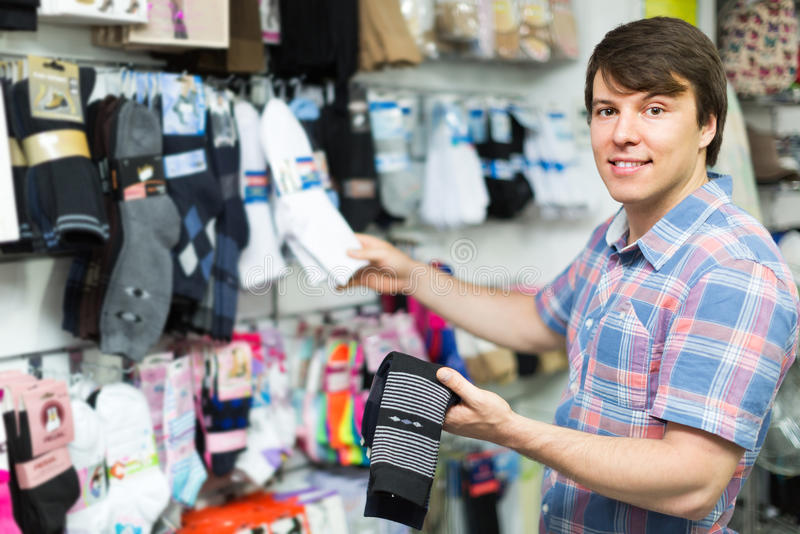 Homme choisissant des chaussettes à la boutique photographie stock libre de droits