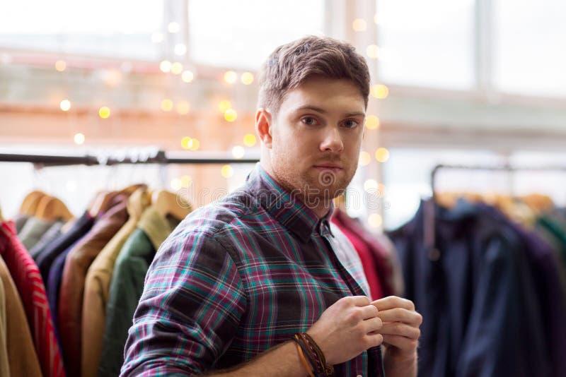 Homme choisissant des vêtements au magasin d'habillement de vintage photos stock
