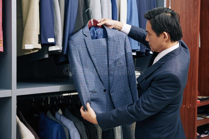 Homme choisissant le costume dans le magasin images libres de droits