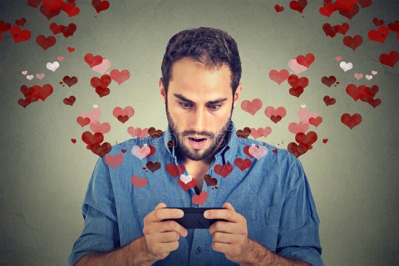 Homme choqué envoyant recevant le message textuel de sms d'amour au téléphone portable photo libre de droits