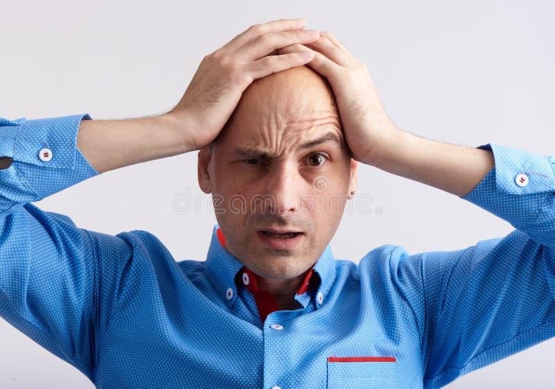 Homme choqué tenant sa tête dans des ses mains image stock