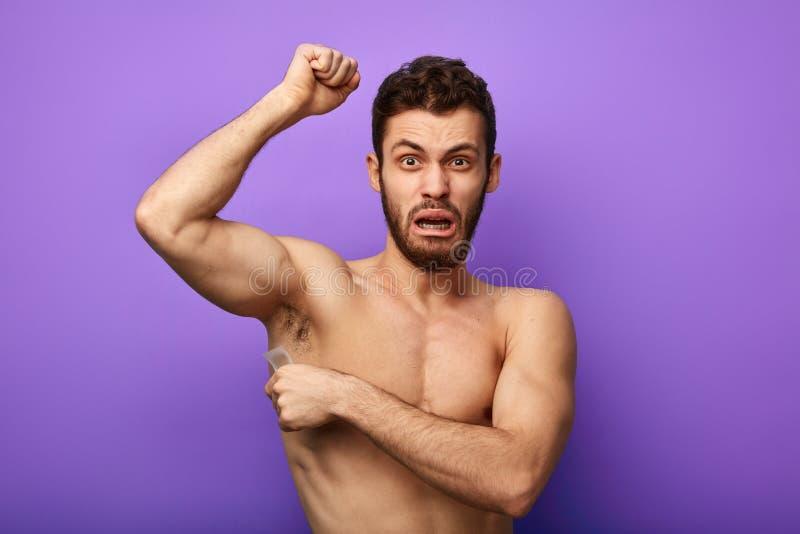 Homme cirant ses aisselles pour épiler des cheveux image stock