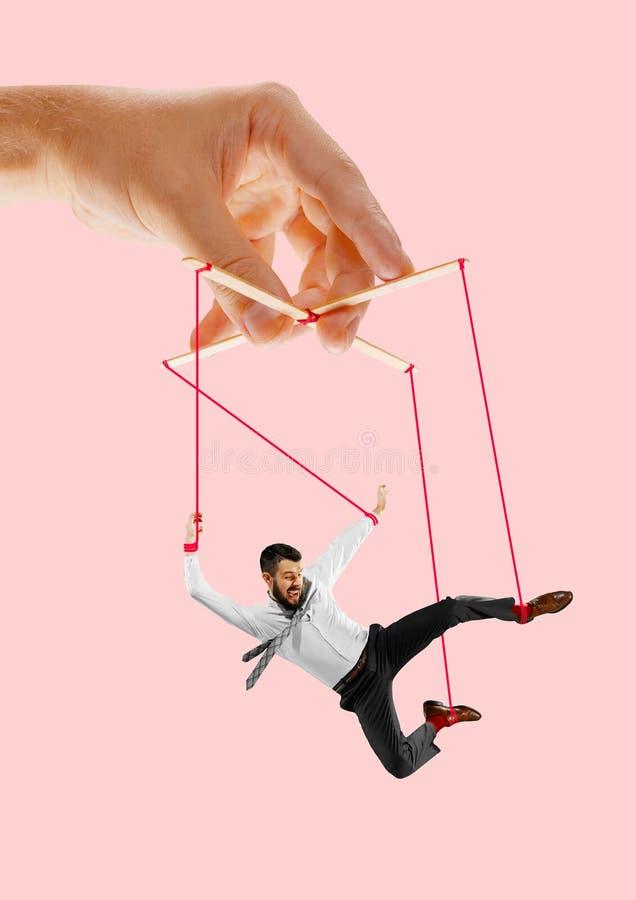 Homme comme une marionnette dans des mains de somebodies Concept de manipulation photo stock