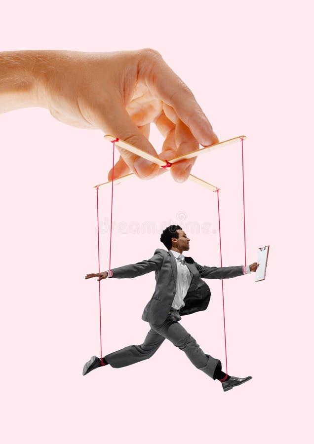 Homme comme une marionnette dans des mains de somebodies Concept de manipulation image stock