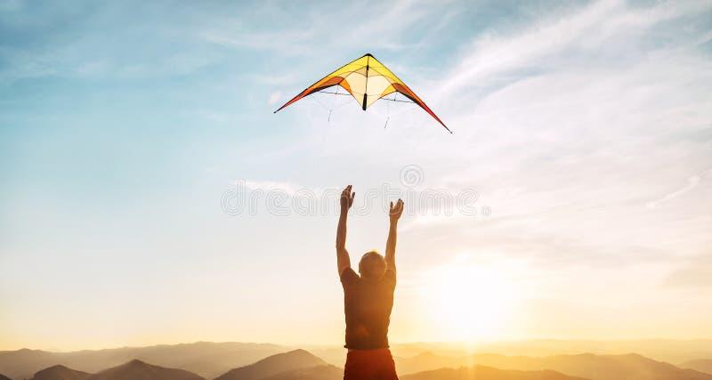 Homme commençant à piloter le cerf-volant lumineux en ciel de coucher du soleil au-dessus de la haute montagne Image de d?marrage photo libre de droits