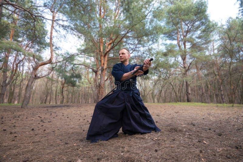 Homme concentré avec une épée japonaise, un katana pratiquant Iaid photo libre de droits
