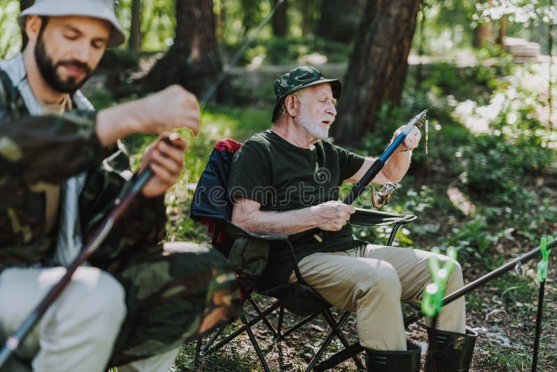Homme concentré mettant une amorce sur le crochet photos stock