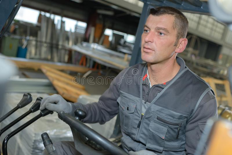 Homme conduisant le chariot élévateur à l'intérieur de l'entrepôt photographie stock