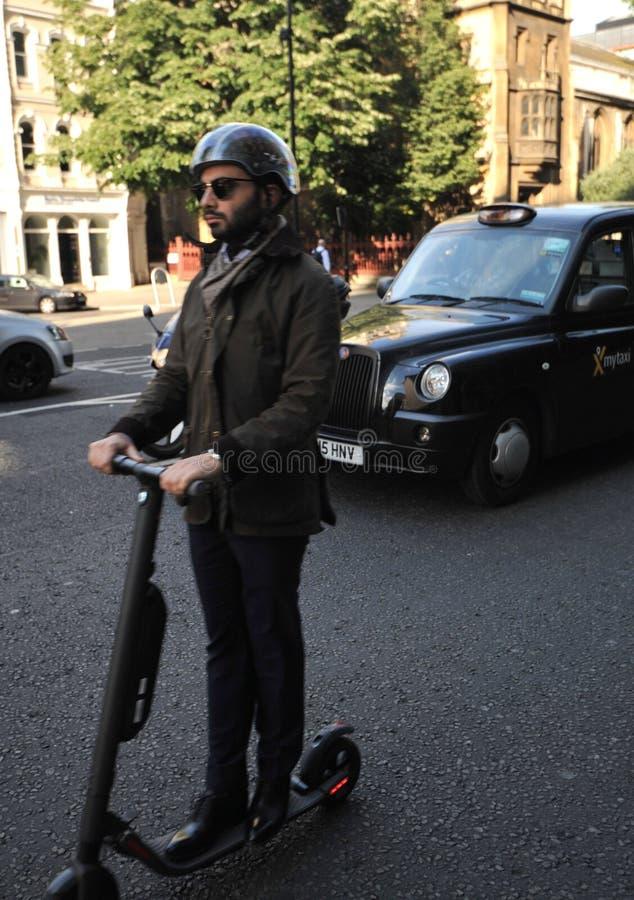 Homme conduisant un scooter électrique sur les rues de Londres, Angleterre photos libres de droits