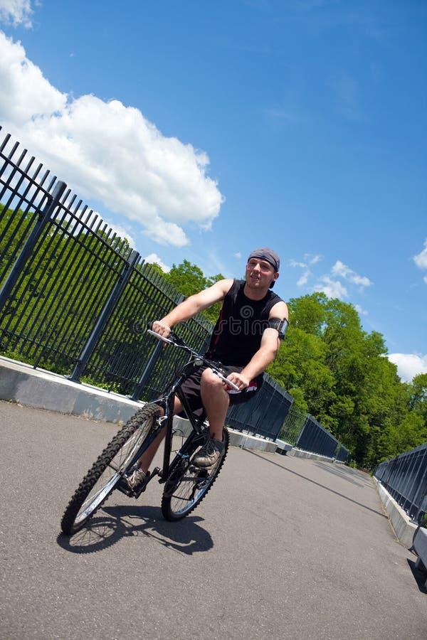 Homme conduisant un vélo image stock